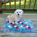 Bowtie quilt table topper with Sadie on it
