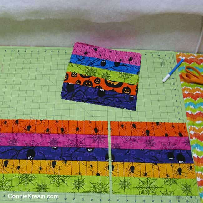 Cutting and sewing the jelly roll strips together for the Eerie Halloween quilt