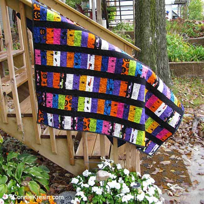 Eerie quilt for Halloween on the neighbors stair rail