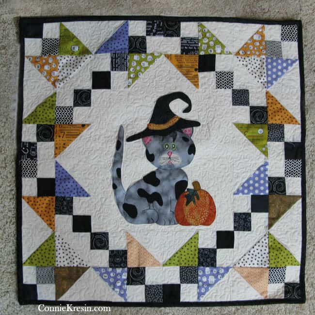 Halloween wall hanging with appliqued kitty in muted colors