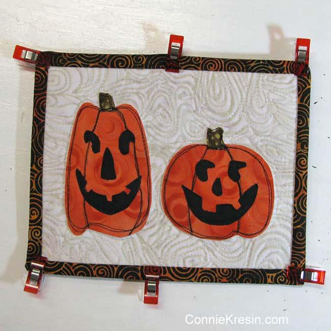 Two pumpkins mug rug using clips to hold the binding