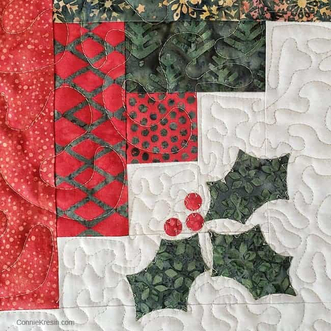 Closeup on Log Cabin quilted wall hanging with applique free motion quilted