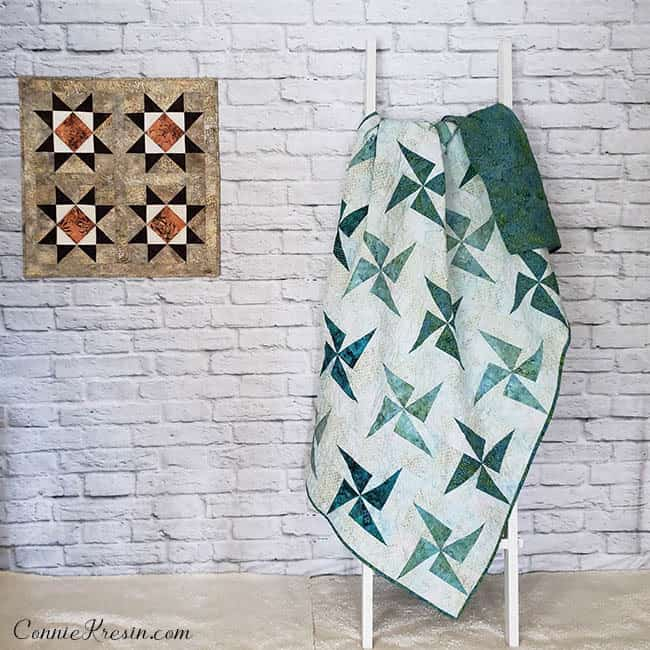 Two AccuQuilt quilts displayed on brick wall