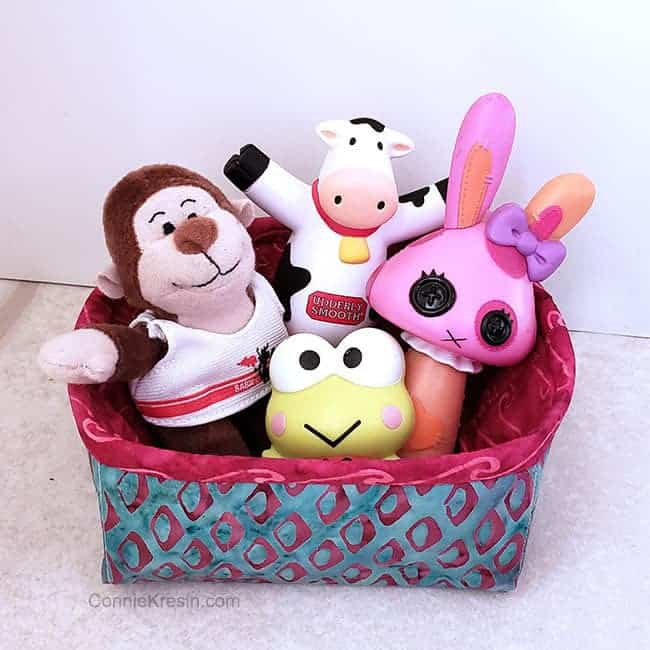 Batik Petit Four basket with toys and stuffed animals in it