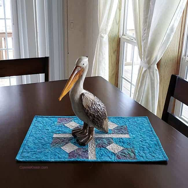 Pelly the pelican sitting on the bow tied table topper