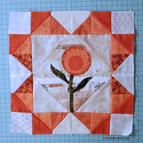 Orange string quilt block with flower applique
