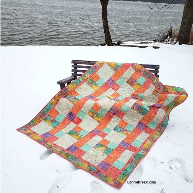 Sorbet batik quilt by the river on bench