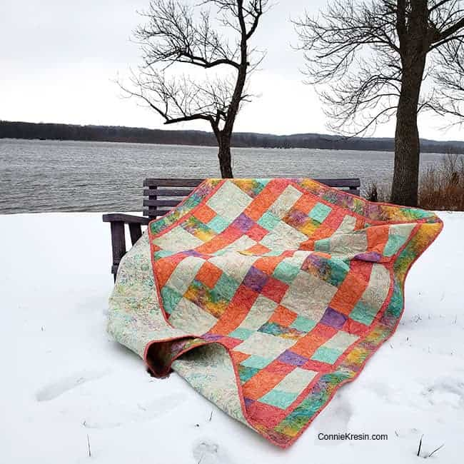 Sorbet batik quilt by the river on bench windy