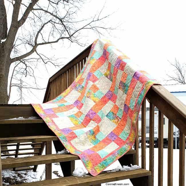 Sorbet batik quilt by the river on deck rail