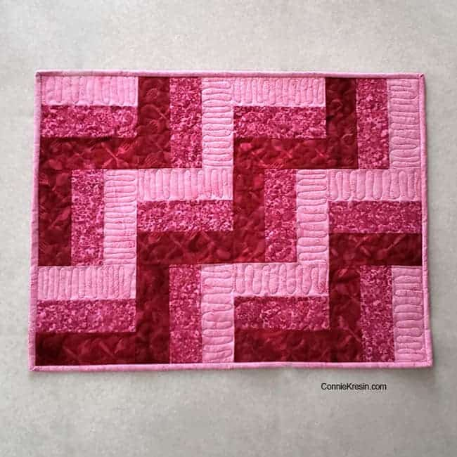 Three by Three easy table topper in pink batiks quilted