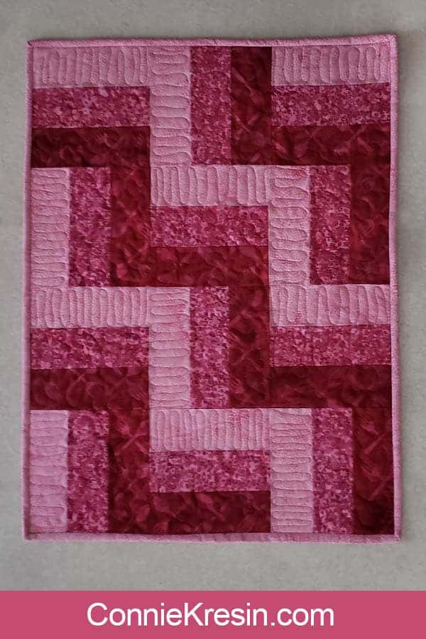 Three by Three easy table topper in pink batiks quilted with Aurifil
