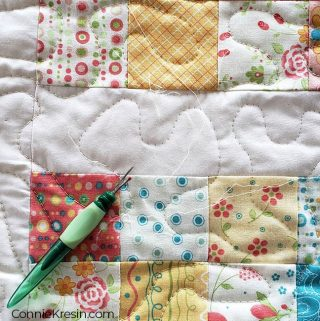 Close up of ripping out the quilt stitching