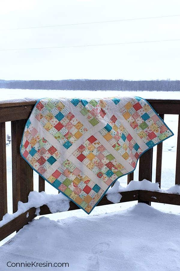 Baby quilt on deck rail by snowy river