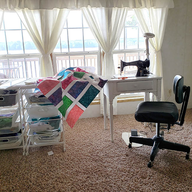 Stack batik quilt with vintage sewing machine in living room