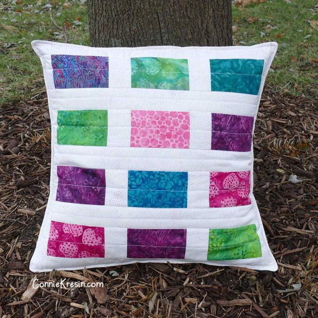 Sparkles pillow by a tree outside