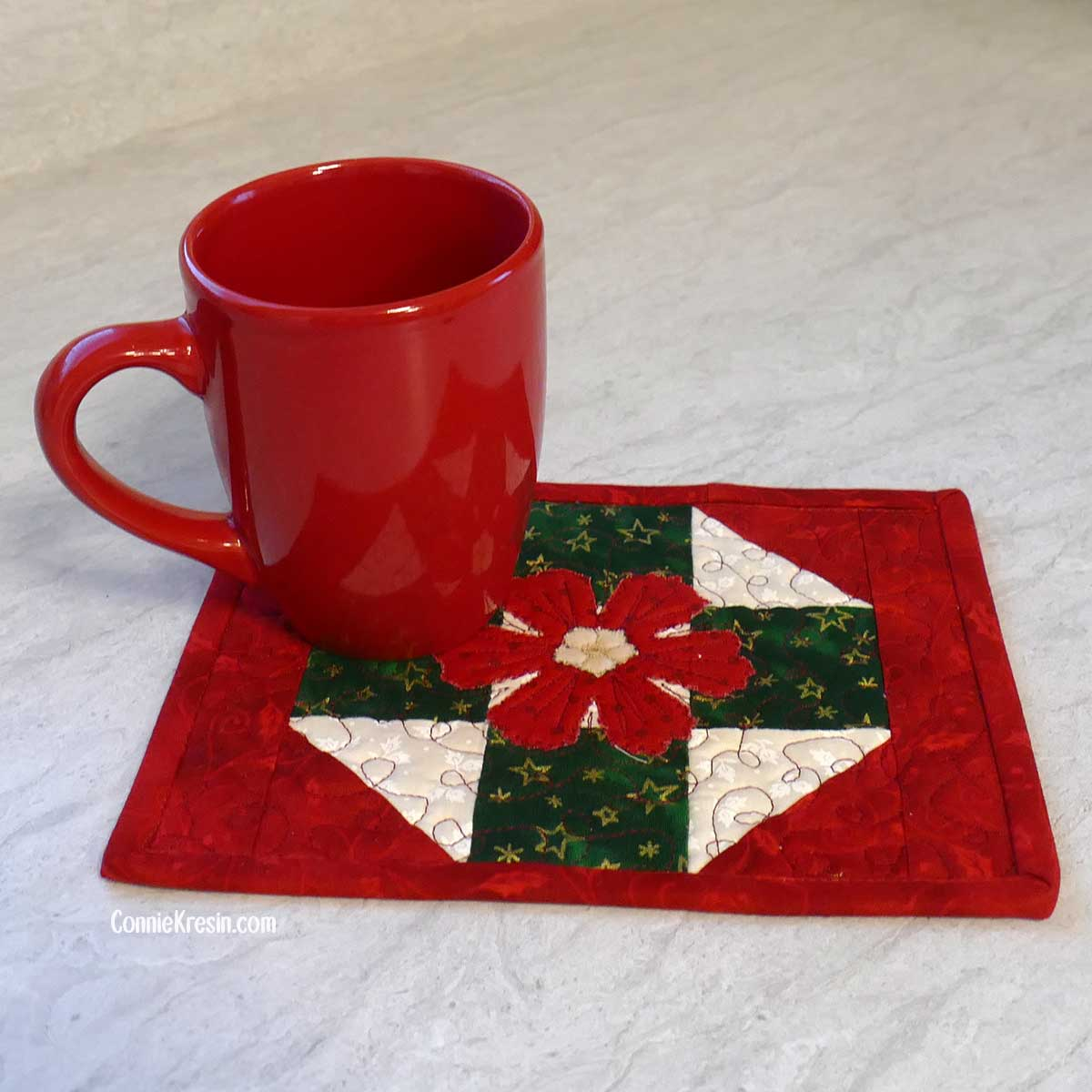 Red coffee cup on the Christmas mug rug