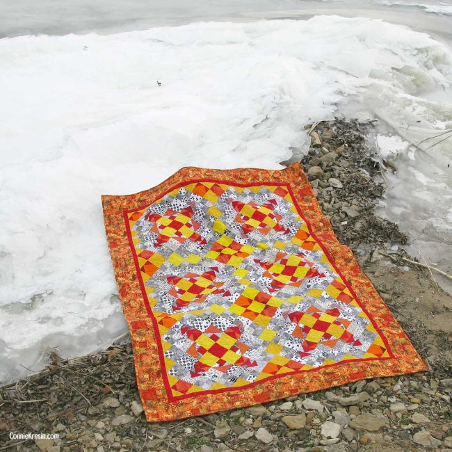Easy Street quilt in orange and yellow on ice