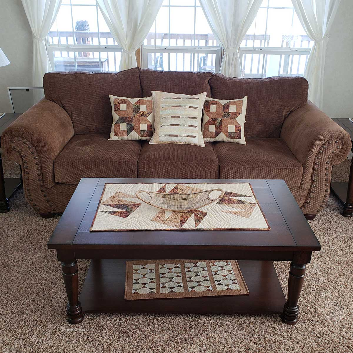 Quilted pillows on couch with table runner on table