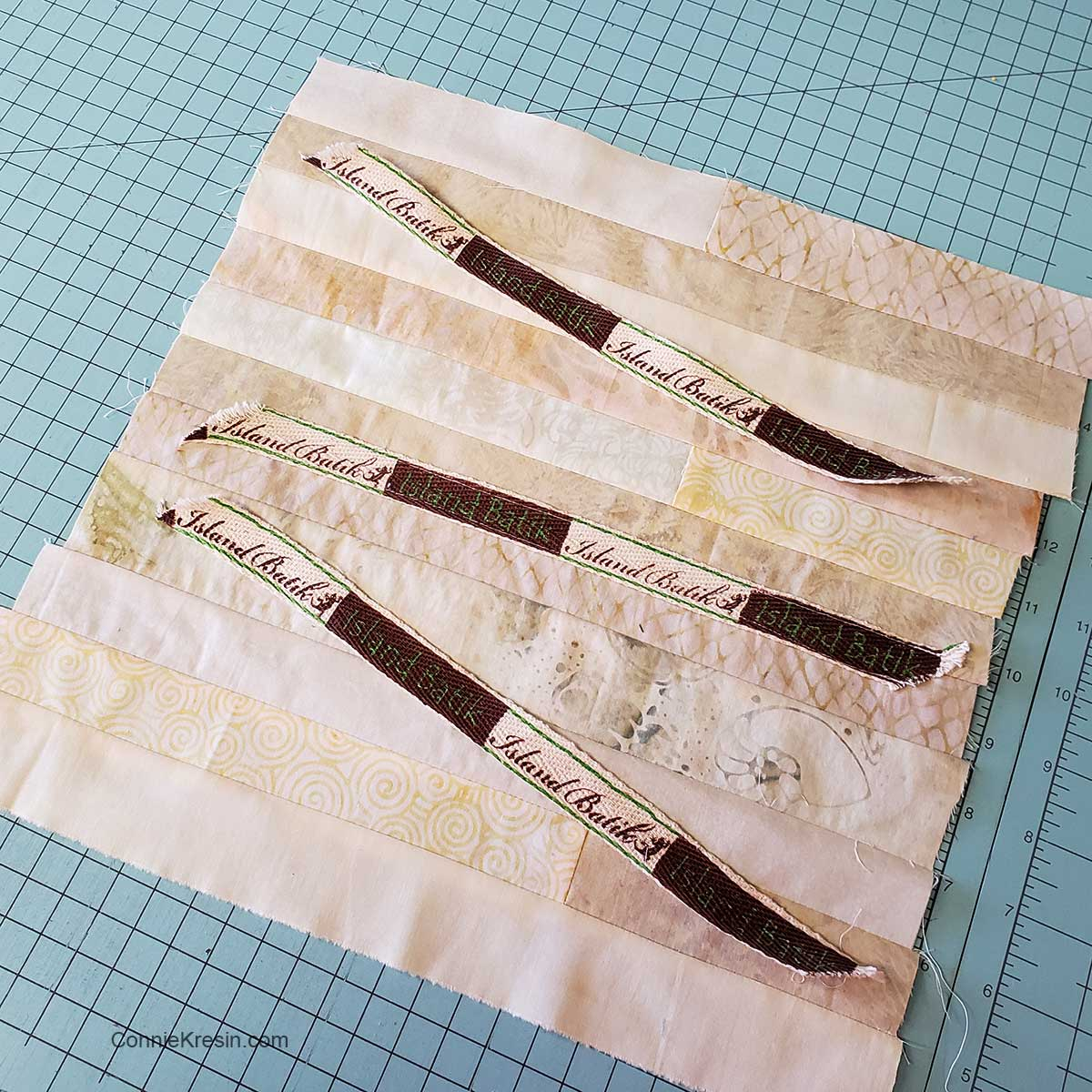 Neutral strips of batiks used to make background for pillow
