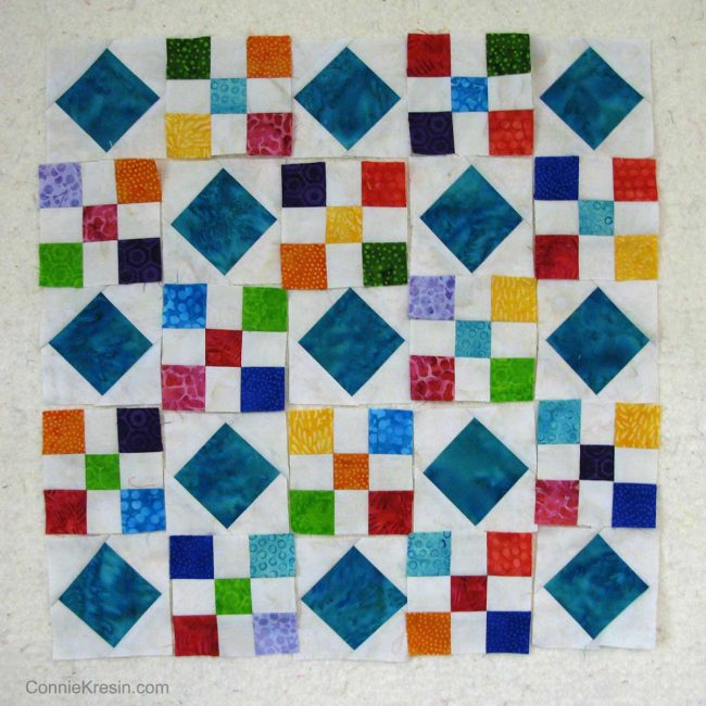 Scrappy batik blocks on design wall