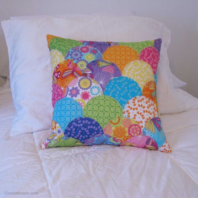 Applique Clamshell pillow on bed with other pillows