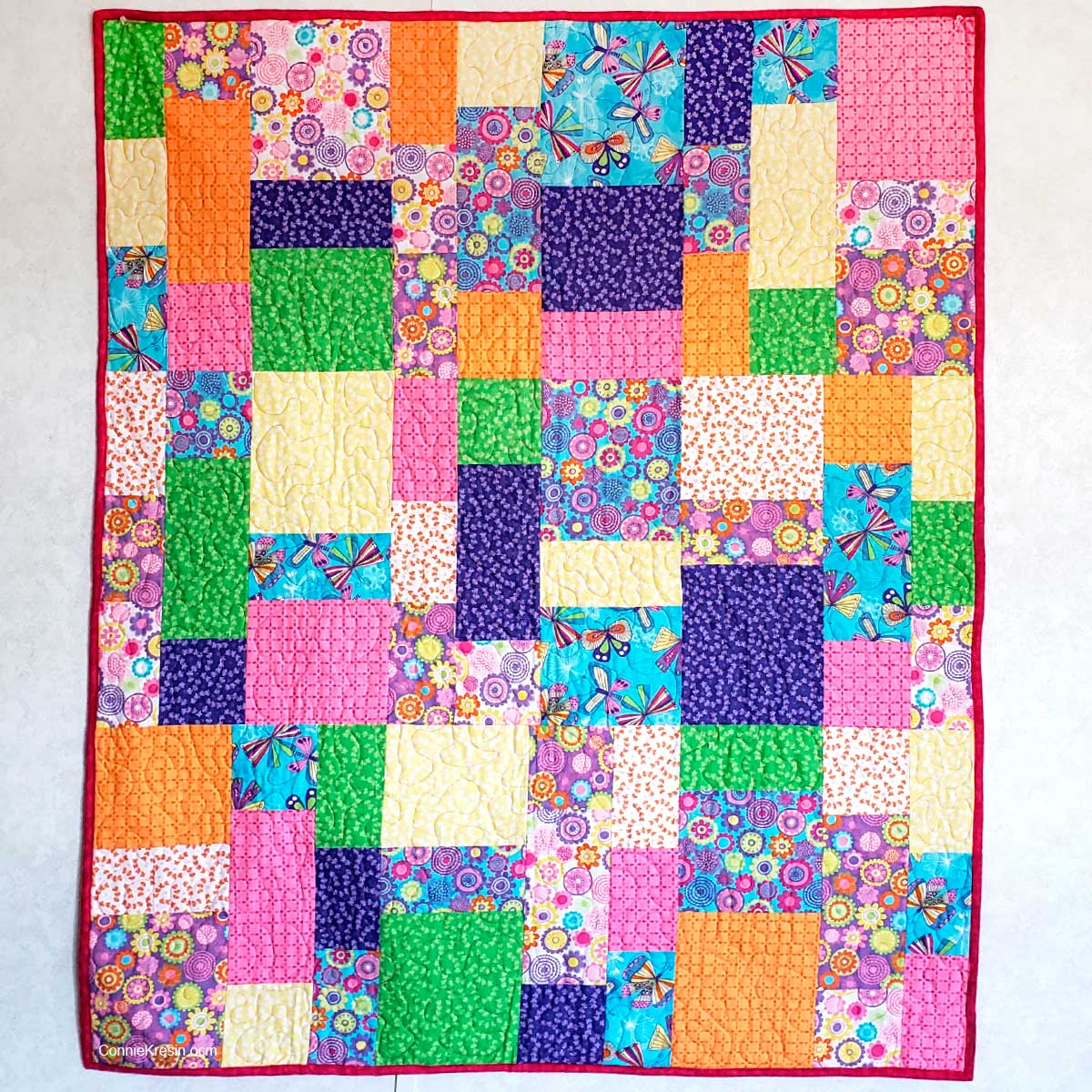 Stacks quilt pattern made with rainbow quilt fabrics for children