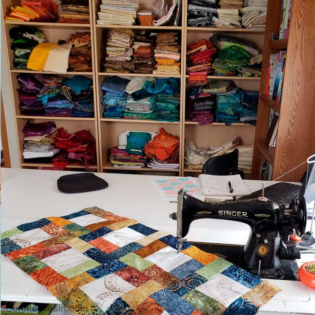 Sew blocks together on sewing machine while looking at fabric stash