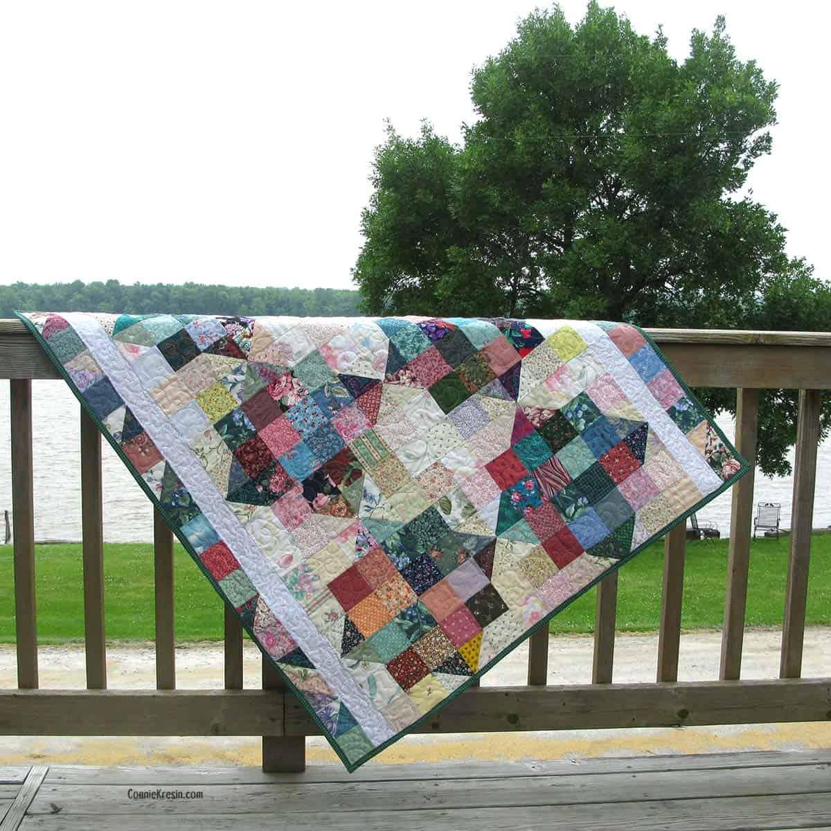 River Scraps baby quilt on deck rail