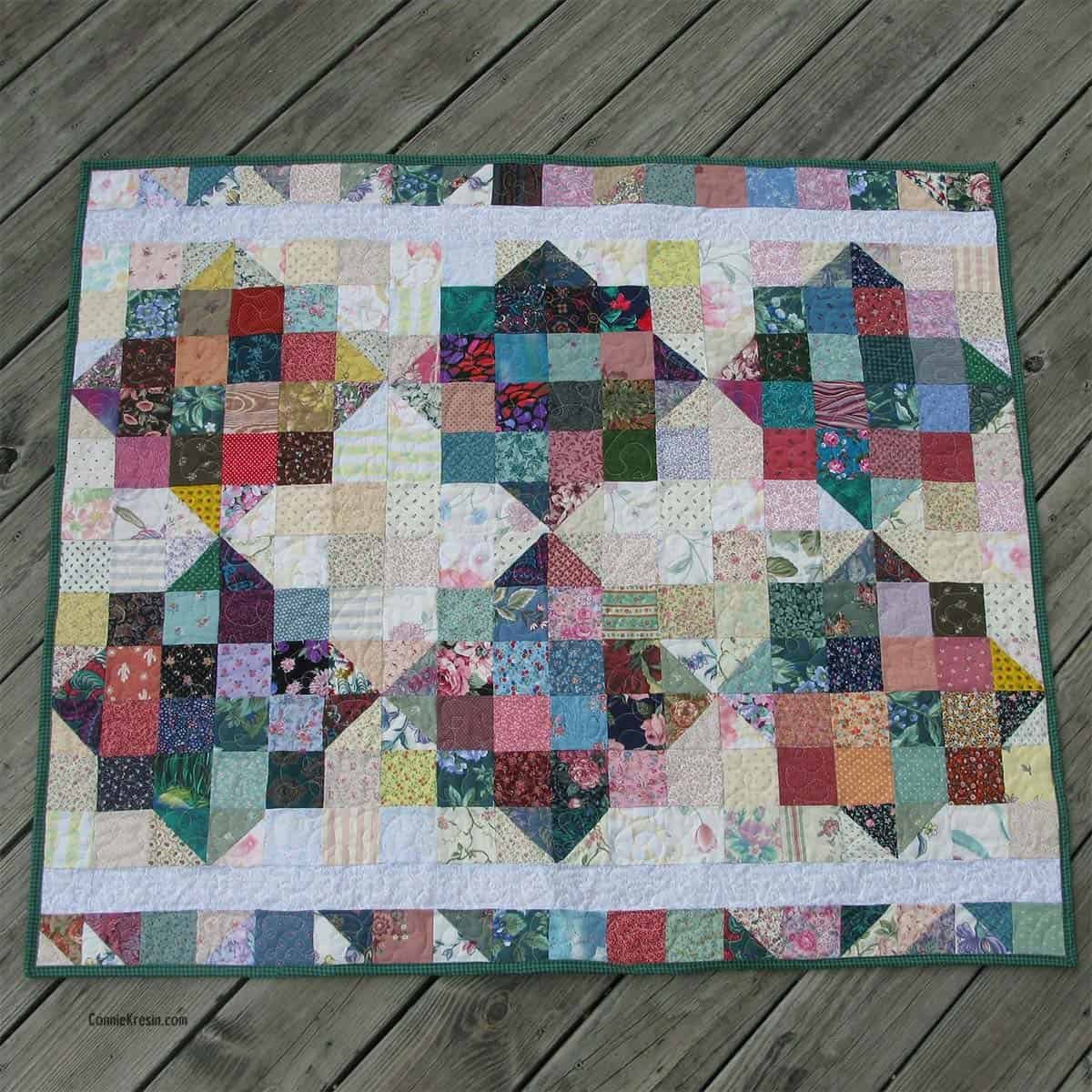 River Scraps baby quilt laying flat on deck