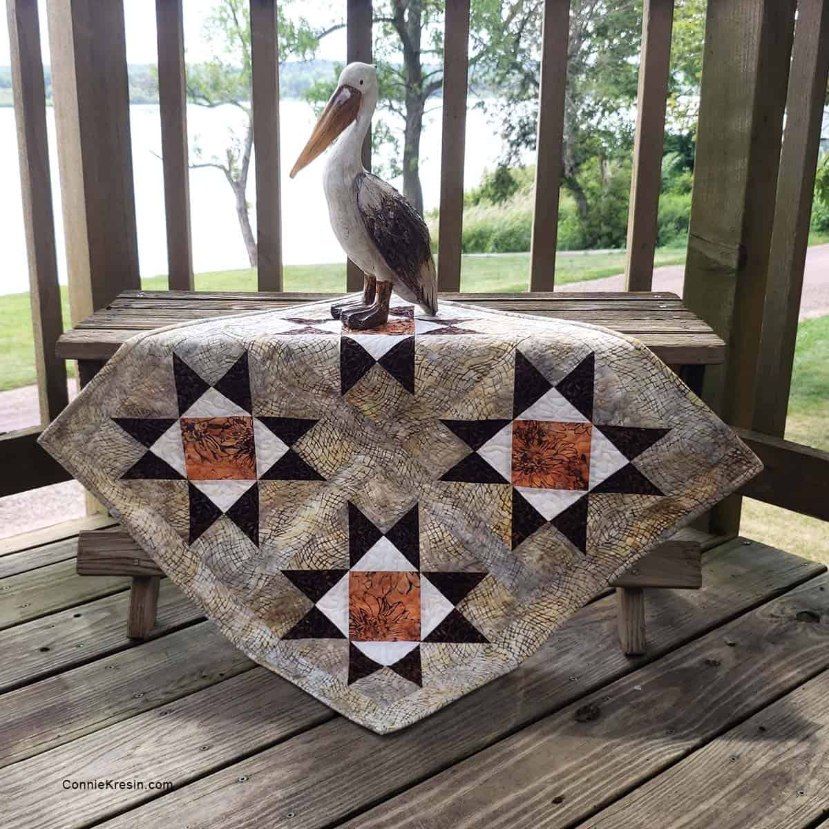 Diamond Stars quilt tutorial with pelican on a bench by the river