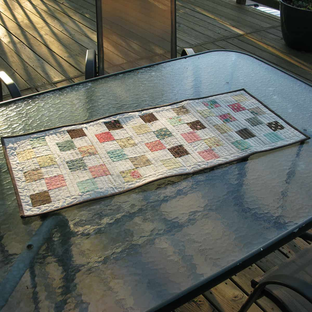 Quilted table runner on deck table