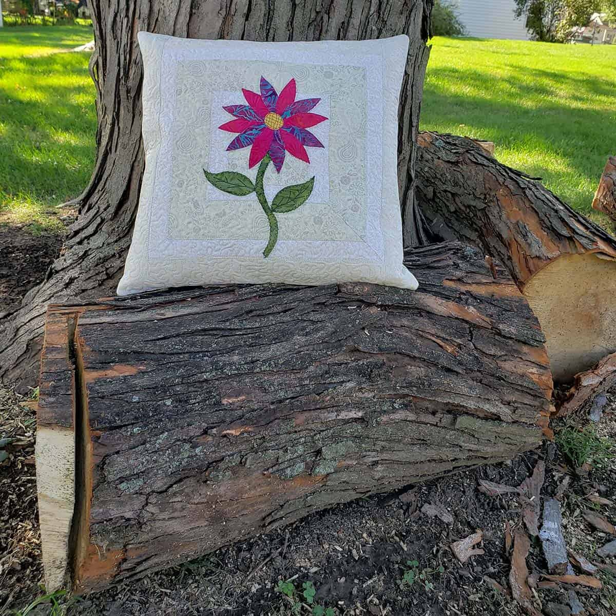 Applique flower pillow by tree trunk