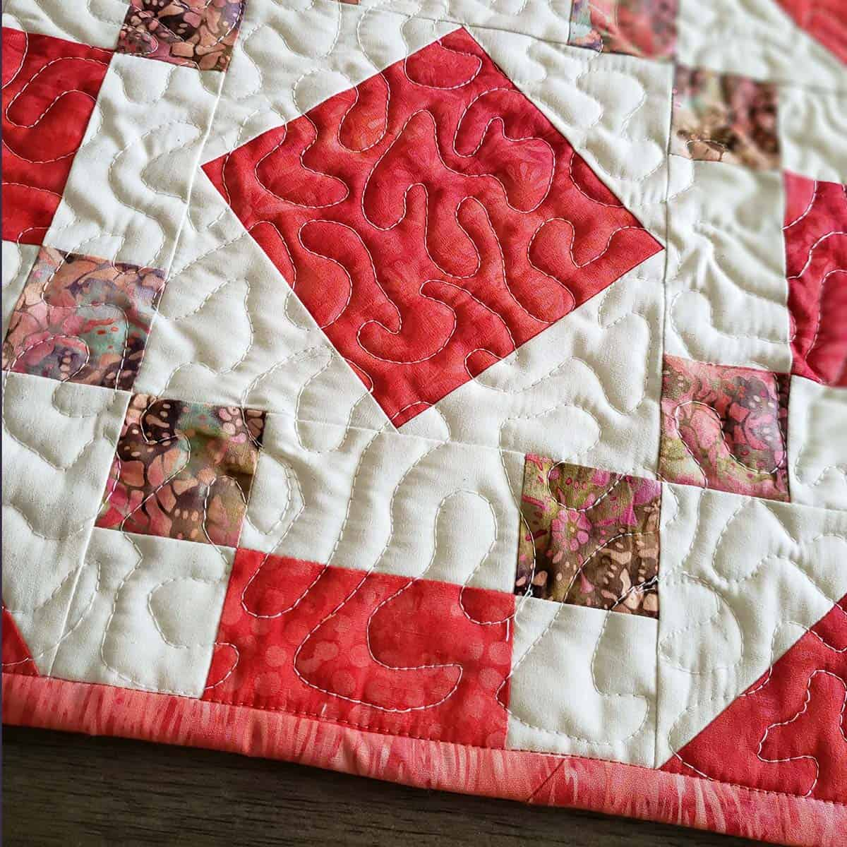 Quilt and bind the coral jewel table runner