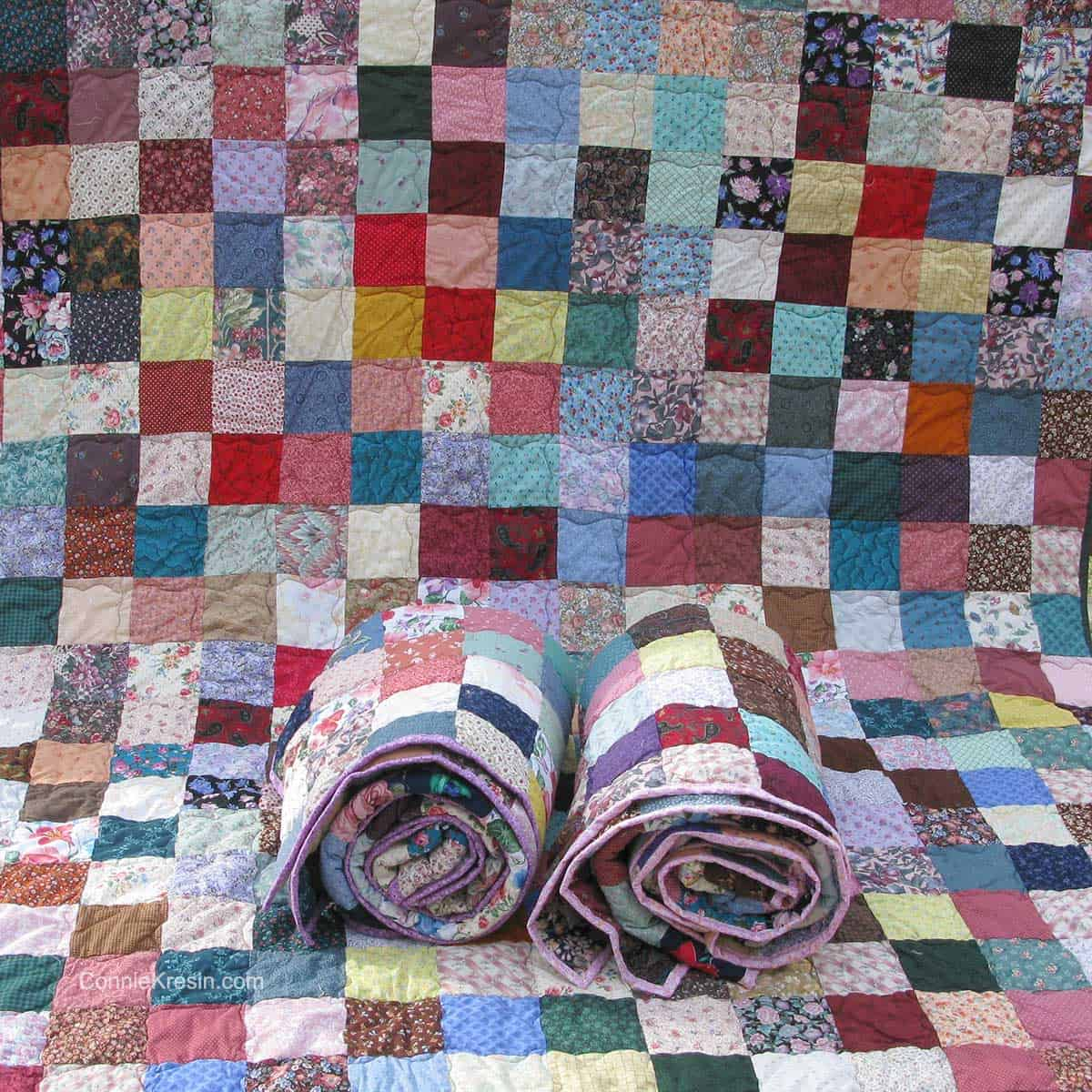 Fast and easy scrappy quilt with 2 more laying on it