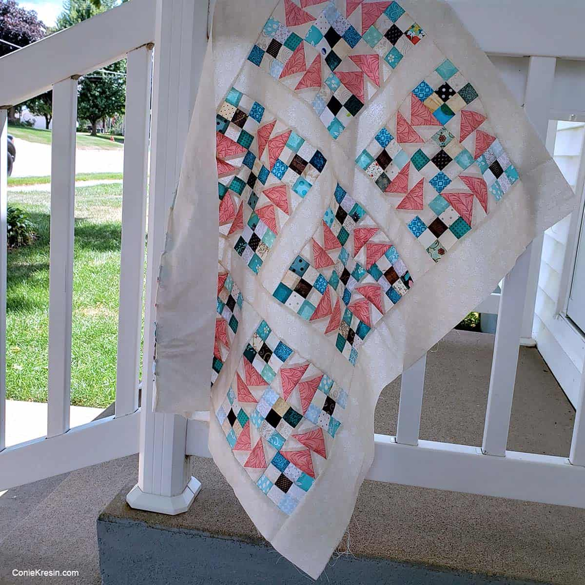 Flying 9 patch baby quilt on railing