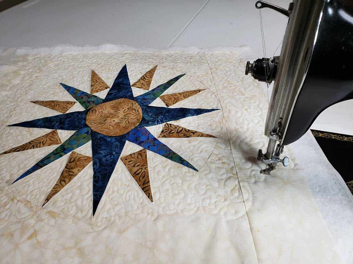 Free motion quilting the Mariner's Compass table topper