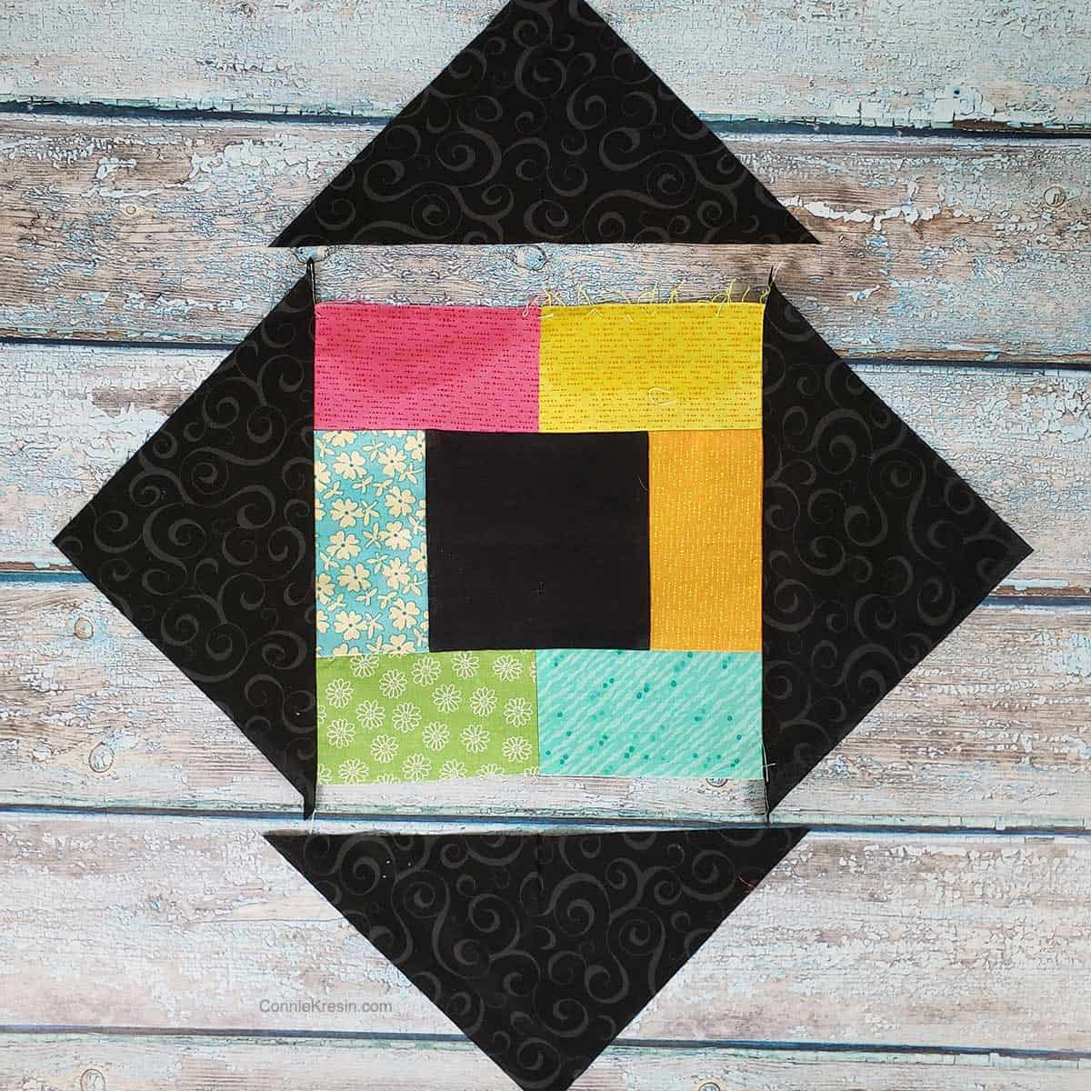 Sewing the corner triangles to the quilt block
