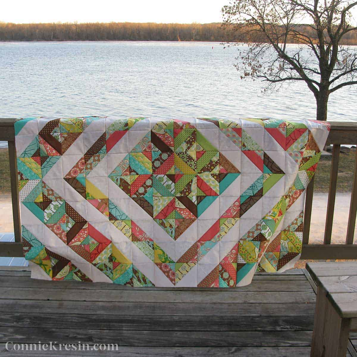 Quilt top on deck rail by the river