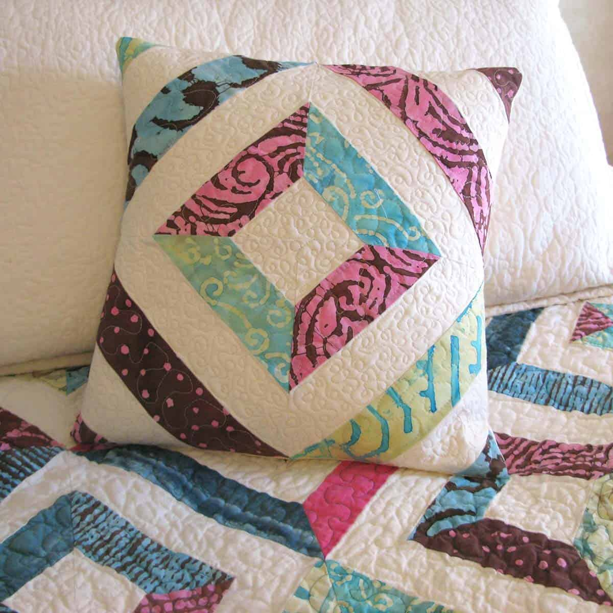 Petunia Strings pillow on quilt