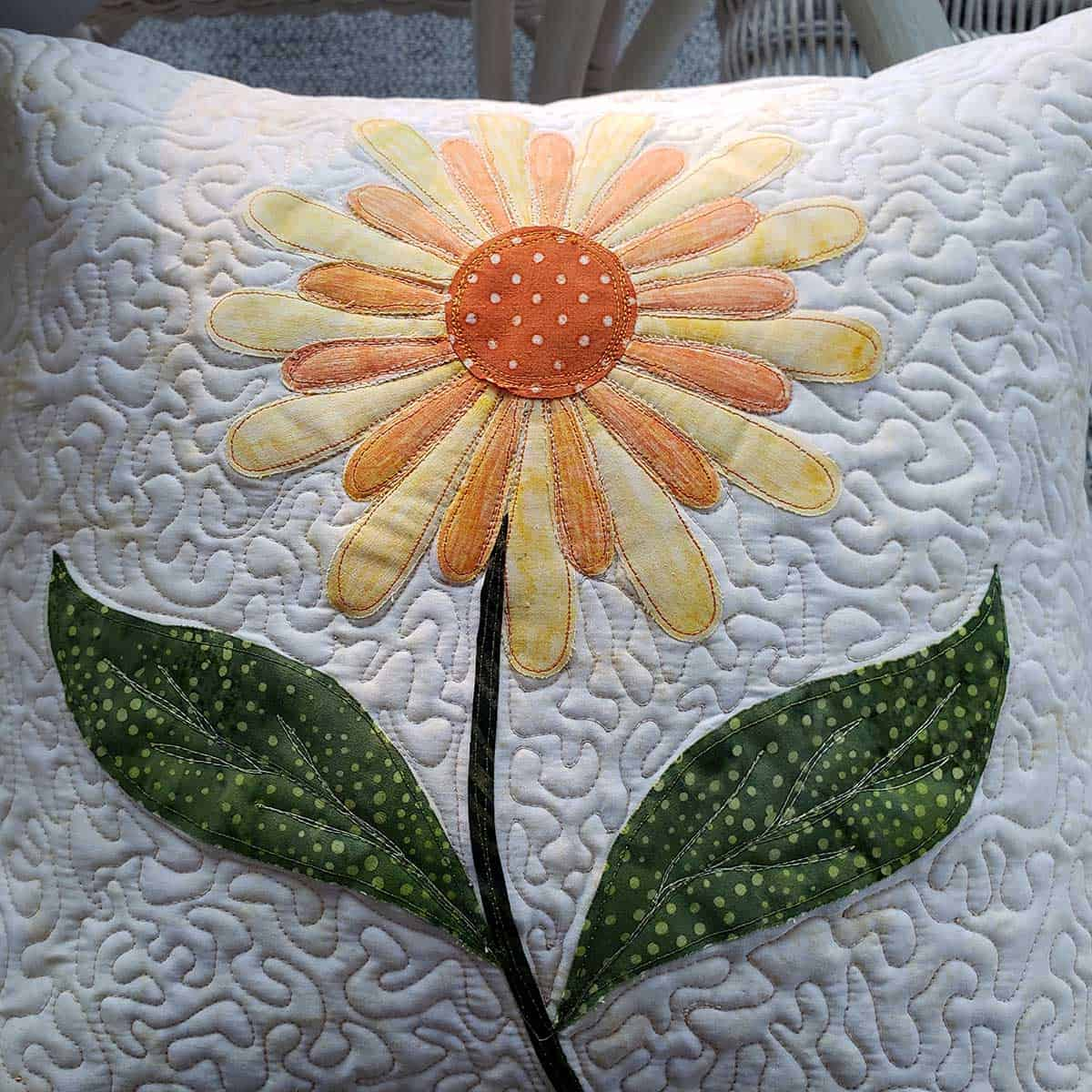 Close up of stipple quilting on the daisy pillow