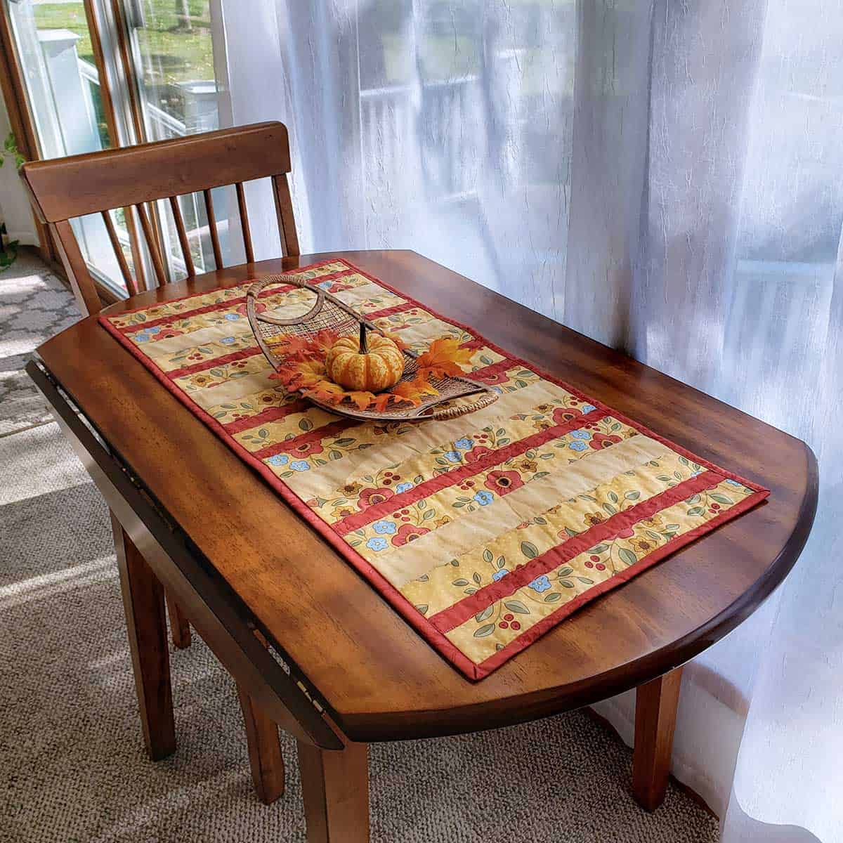 Easy quilted yellow striped table runner on table