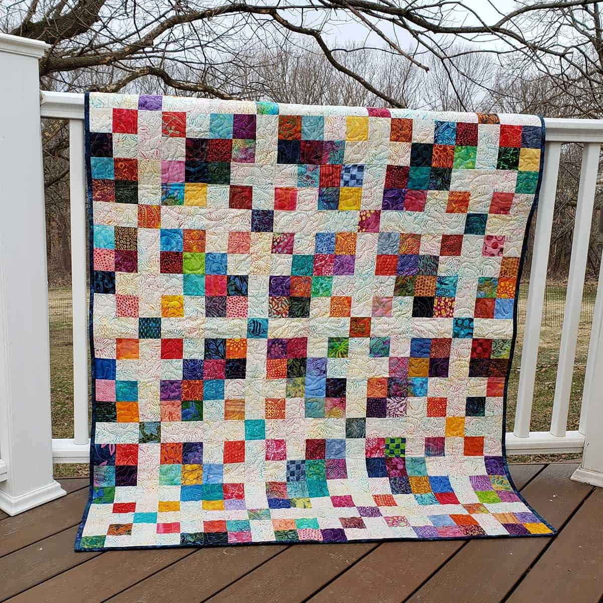 Scrappy Block quilt on deck rail