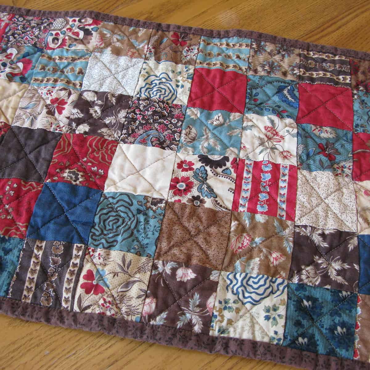 closeup of quilting on vintage chocolate table runner