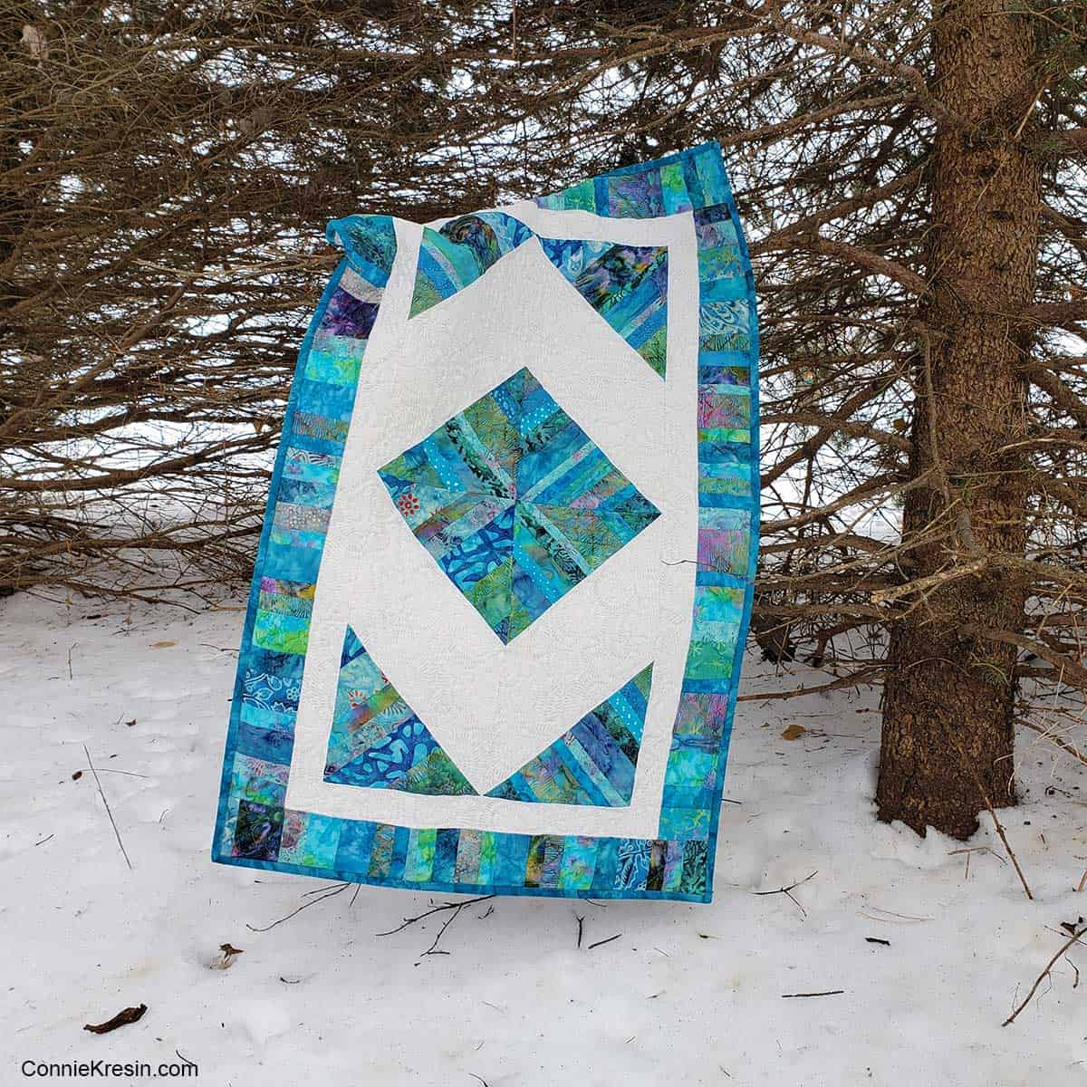 Quilt String Block table runner under a tree in the woods